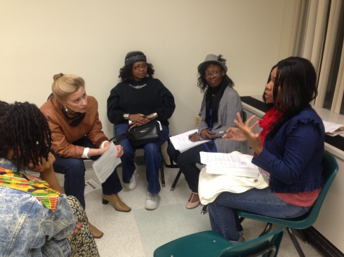 Kate intently listening and Power Coaching Tyesha, Charmelle, Annette, Tenisha and Kira.